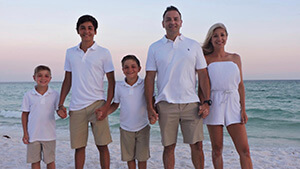 family of mann eye employee that had LASIK standing on the beach wearing white
